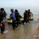 https://www.euractiv.com/wp-content/uploads/sites/2/2015/08/spanish_tourist_watches_immigrants_arrive_at_island_of_kos.jpeg